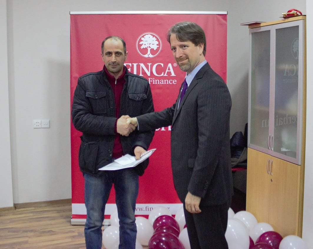 FINCA Azerbaijan CEO Timothy Tarrant meeting with client during ceremony to open new Agsu branch.